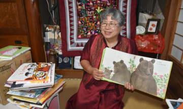 私費を投じてラオスに図書館を建設した関谷康子さん。寄贈する絵本を手に「未来を切り開く一冊に出会える場所にしたい」と目を輝かせる=日南市吉野方