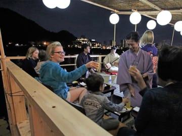 試験的に設置された桟敷で鵜飼観覧などを楽しむ外国人観光客ら=岐阜市長良、長良川河畔