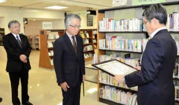 杉浦館長(右)から感謝状を受ける岡部副代表理事(中)。左は梅津事務局長