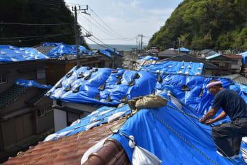 ブルーシートが風に飛ばされないように土のうを取り付ける久保田さん=8日午前10時45分、鋸南町岩井袋