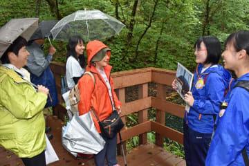十二湖の人気スポット・青池で観光客を案内する木造高深浦校舎の生徒たち(右)