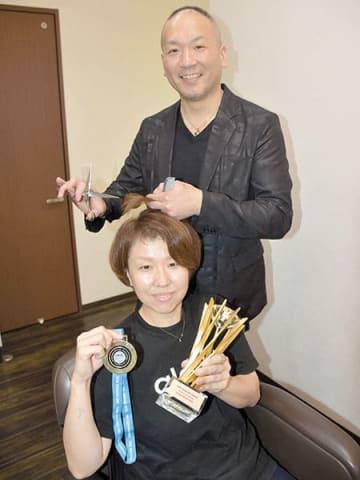 世界一のトロフィーと金メダルを手にした妻・祐子さんの後方で、はさみを手に笑顔を見せる山崎桂さん=2日、さいたま市北区植竹町1丁目の「glaux」