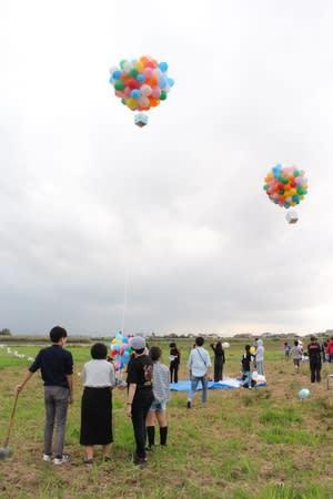 気球を模した風船を空に浮かべたアート作品=新潟市北区