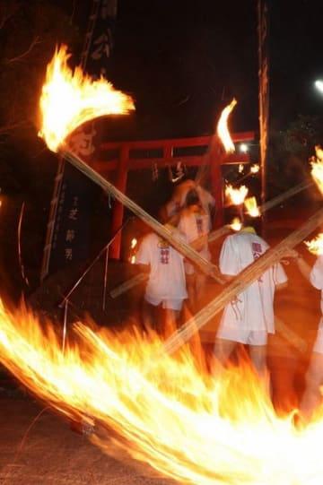 約30人の青年がたいまつを手に神社に参った(8日、和歌山県串本町樫野で)