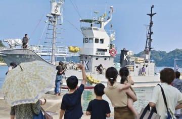 家族らが出迎える中、太地漁港に戻った第7勝丸(8日、和歌山県太地町で)