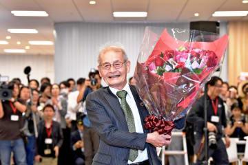 大勢の社員や報道陣に囲まれてノーベル化学賞の受賞を喜ぶ吉野彰さん=9日午後7時25分ごろ、旭化成東京本社