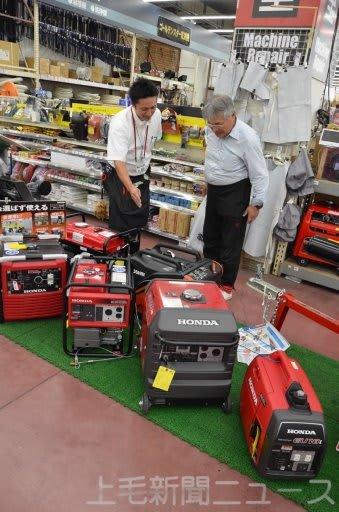 売り場に並ぶ発電機の特徴を担当者が説明=ジョイフル本田新田店