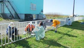フェンスの塗装奉仕に取り組む技能士会員ら