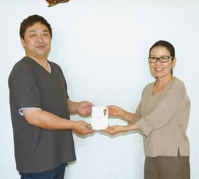 伊藤代表理事に寄付金を手渡す桔梗原実行委員長(右)