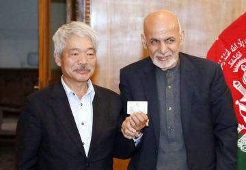 アフガニスタンのガニ大統領(右)から市民証を渡される中村哲医師=7日、カブール(アフガニスタン大統領府提供)