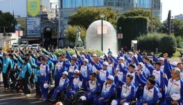 結団壮行式で拳を突き上げ、健闘を誓う選手たち=JR岡山駅東口広場