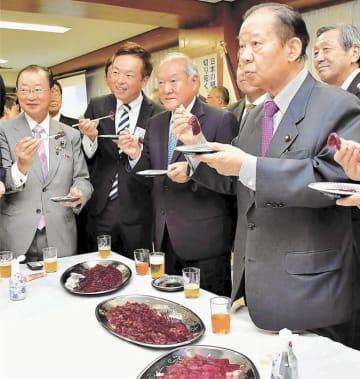 ニタリクジラの刺し身を試食する(右手前から)二階氏、鈴木氏ら=9日、自民党本部