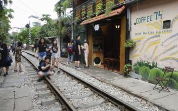 ベトナム・ハノイ中心部の線路で写真を撮る若者ら=9日(共同)