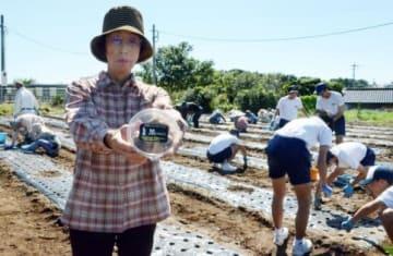 オリジナルの黒ニンニクと、ニンニクの植え付けをする生福地区まちづくり協議会のメンバーら=いちき串木野市生福