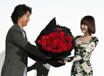 伊藤健太郎さん(左)からバラの花束を受け取る玉城ティナさん