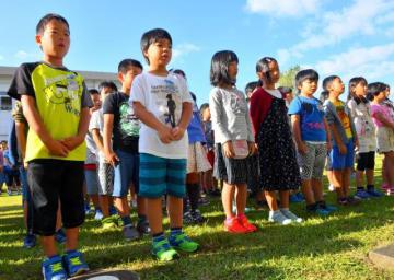 秋空の下、校庭で行われた終業式に臨む児童たち=10日午前、宮崎市・池内小