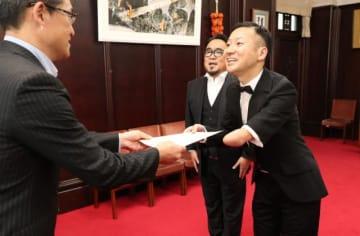 「国文祭・芸文祭みやざき2020広報アンバサダー」の委嘱状を受け取るこんやしょうたろうさん(右)と井尻慶太さん(中央)=10日午前、県庁