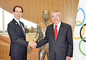 近代五輪の始祖クーベルタン像の前で握手を交わす内堀知事(左)とバッハ会長=10日、ローザンヌ・IOC本部