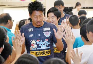 児童とハイタッチする豊田陽平選手(手前)らサガン鳥栖の選手たち