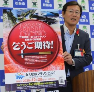 【「みえ松阪マラソン」応援隊の募集ポスターを掲げる竹上市長=松阪市役所で】