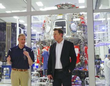 「スペースX」の有人型ドラゴン宇宙船(後方)を視察後、開発状況を話すNASAのブライデンスタイン局長(左)=10日、米カリフォルニア州ロサンゼルス近郊(共同)
