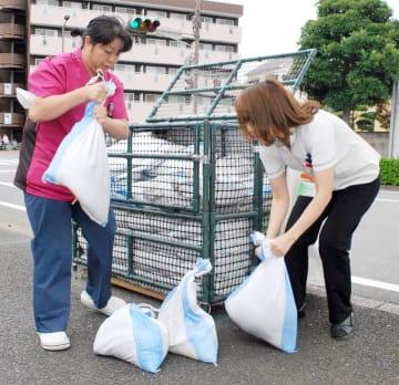 台風19号の高潮に備え市の土のうステーションから土のうを運び出す女性=10日午後4時ごろ、千葉市中央区