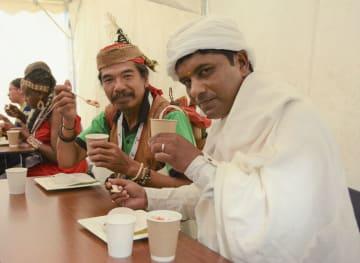 札幌市で開かれたイベントで、アイヌ料理を食べる少数民族の男性ら=11日午後