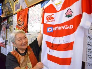 リーチ・マイケル主将のサイン入りユニホームを持つ黒岩敬子さん=鹿児島市高麗町の「らーめん家」