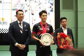 成澤廣修文京区長(左)、佐藤敏信監督(右)と記念撮影に応じる服部選手。=文京シビックセンターで