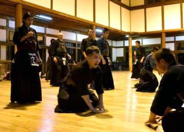 県内の剣道家との稽古を終え、お礼のあいさつをするアジアの剣道家ら=10日午後、宮崎市天満町の県警察学校・武徳殿