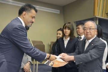国連総会第1委員会のヨレンティ議長(左)に「ヒバクシャ国際署名」の目録を提出する被団協の藤森俊希事務局次長=11日、ニューヨークの国連本部(共同)