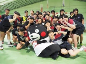 くまモンと一緒に写真に納まる女子ハンドボール日韓U16代表の選手たち=山鹿市