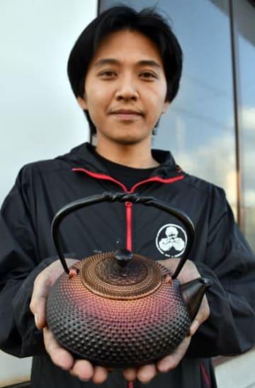 ブラックホールをイメージして製作した南部鉄器の急須を手にする菊地海人さん