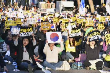 12日、ソウルの検察庁舎近くで開かれた集会でプラカードを掲げる参加者(共同)