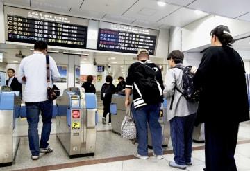 東海道新幹線がおおむね時刻通りの運行開始となり、早朝から改札を通る人たち=13日午前5時50分、JR東京駅