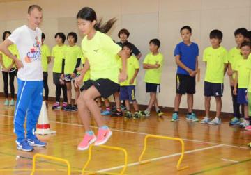 ミニハードルを飛ぶ練習を指導するウラジオストク市チームの選手(左)=12日、境港市誠道町