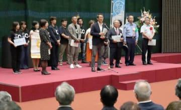児童虐待防止に向け、あいさつする榊区長(中央)とゼロ会議のメンバーら(後方)=11日、大阪市浪速区