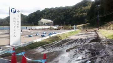 ナミビア―カナダ戦が中止となった釜石鵜住居復興スタジアム。関係者駐車場に続く道路が土砂に覆われた=13日午前10時3分