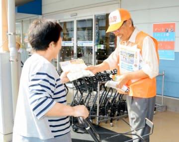 道の駅利用者に啓発パンフレットを手渡す参加者(右)
