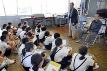 疎開体験者の川迎和男さん(左)と牧瀬渉さんの話に耳を傾ける下西、山野両小学校の6年生=西之表市西之表