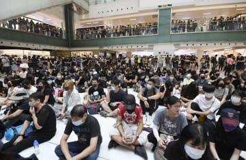 香港・新界地区のショッピングモールで座り込んで抗議する市民ら=13日(共同)