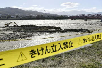 台風19号による大雨で千曲川が氾濫し、河川敷に張られた立ち入り禁止のテープ=13日午後2時9分、長野県上田市