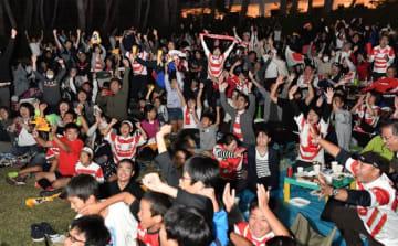 日本が初の決勝トーナメント進出を決めた瞬間、喜びを爆発させるファンたち=13日午後、宮崎市のフェニックス・シーガイア・リゾート