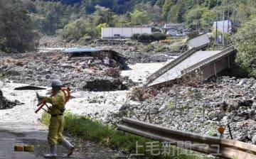 吾妻川に崩落した国道144号。濁流は近くの自動車整備工場や資材置き場ものみ込んだ=13日午前11時35分ごろ撮影、嬬恋村