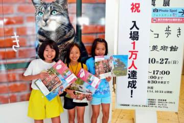 「岩合光昭の世界ネコ歩き」で入場1万人目になった(右から)玉城さん、屋嘉比さん、金城さん=13日、浦添市美術館