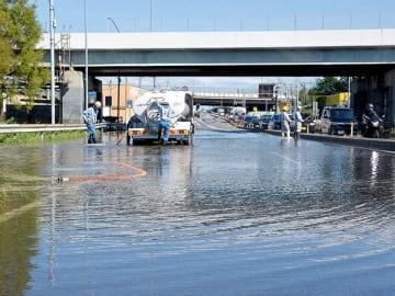 冠水した国道16号の排水作業を行う作業員=13日午後1時ごろ、さいたま市岩槻区加倉