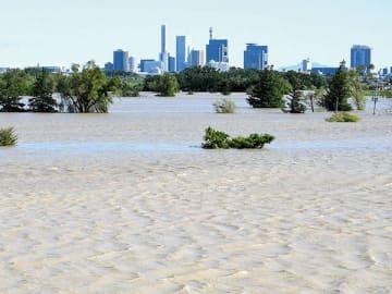 荒川右岸、羽根倉橋付近から見たさいたま新都心方面。手前にある野球場など運動場は全て荒川の増水によって水没している=13日午前9時半ごろ