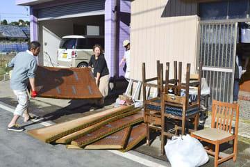 【住宅が床上浸水し、水に漬かった畳を運び出す住民ら=志摩市大王町畔名で】