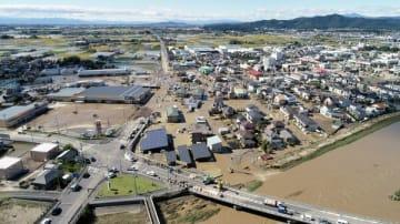 秋山川の堤防決壊(右下)で浸水した住宅街=13日午後0時35分、佐野市寺中町、小型無人機から