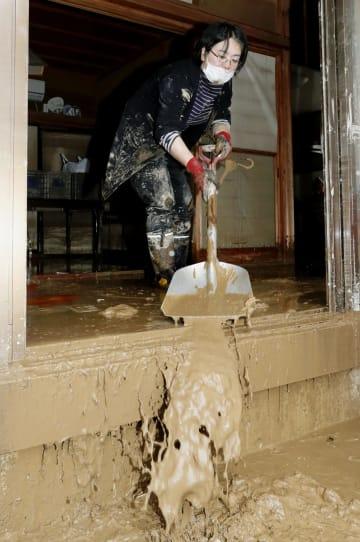 台風19号の影響で自宅が浸水し、たまった泥をかき出す女性=14日午前11時38分、長野市豊野地区